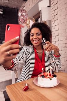 Per i social network. felice donna allegra che scatta foto sul suo telefono mentre desidera pubblicarle su internet