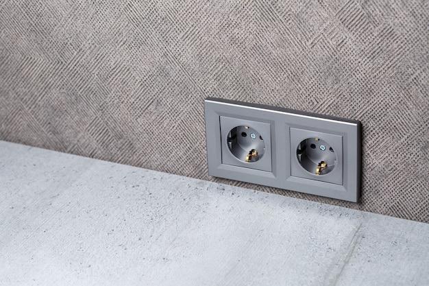Presa grigia con massa con ingresso per due dispositivi. è sulla parete grigia sopra il tavolo da conteggio. elettricità e concetto di riparazione