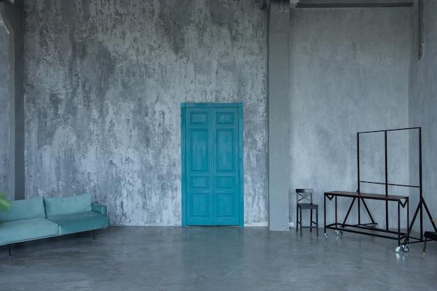 Un appendiabiti per divano e una porta acquamarina contro un muro di cemento