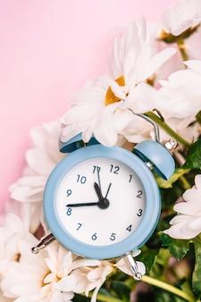 Una sveglia blu tenue in un bouquet di margherite. concetto floreale per le vacanze