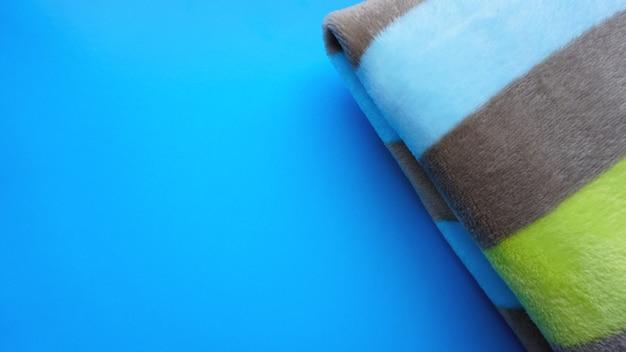 Morbida coperta blu, plaid su sfondo blu. comfort autunnale, spazio per il testo, vista dall'alto strato piatto con copia spazio per slogan o testo, cuscini decorativi, gabbia