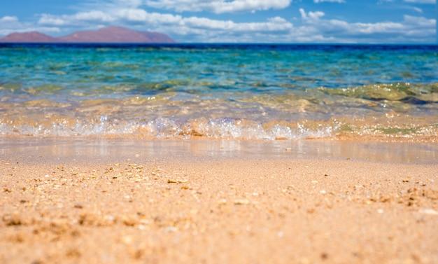 Onda di oceano blu morbida o mare limpido sul concetto di estate di spiaggia sabbiosa pulita. bella scena dell'oceano della spiaggia con l'onda blu sulla spiaggia con la riflessione dei raggi del sole sull'acqua. copia spazio