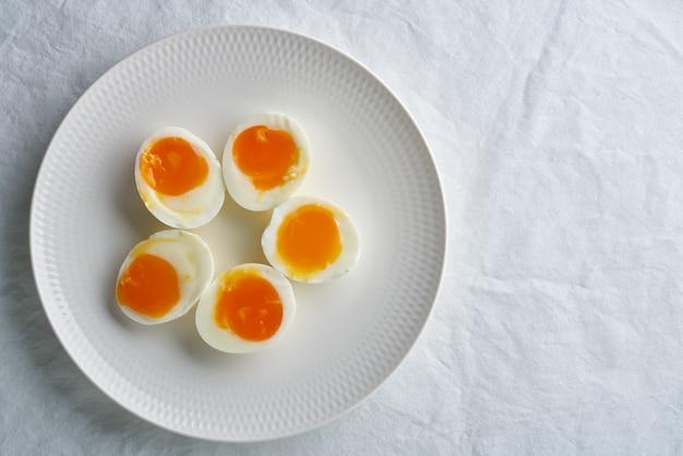 Uova alla coque, sbucciate e tagliate in due metà, distese sul piatto bianco, copia dello spazio