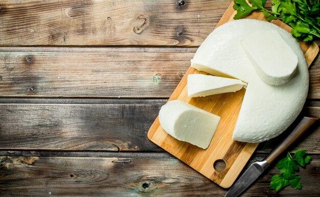 Formaggio a pasta molle con un ramo di menta sulla tavola di legno.