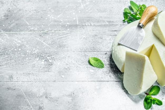 Formaggio a pasta molle con foglie di menta. su un tavolo rustico.