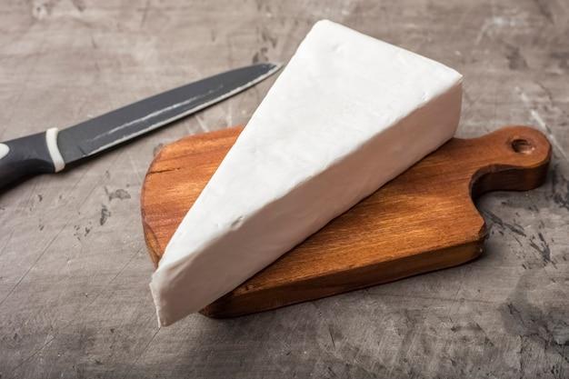 Formaggio a pasta molle con muffa bianca su un tagliere di legno. decorato con prezzemolo verde