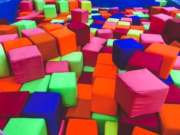 Cubi morbidi nella piscina asciutta della stanza dei bambini del gioco per bambini.