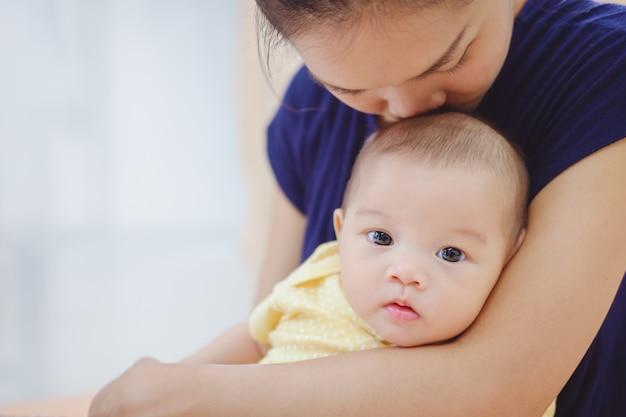 Flou su madre asiatica che tiene e bacia il suo bambino
