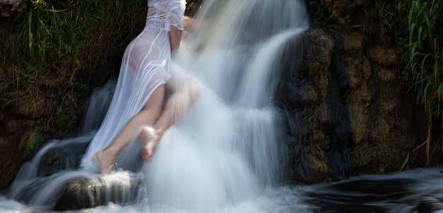 L'immagine sfocata con messa a fuoco morbida di una giovane donna seminuda in abito bianco gode della freschezza e della freschezza nei getti d'acqua della cascata
