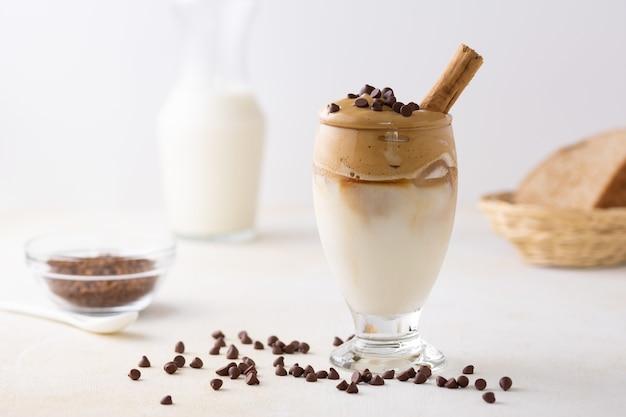 Soft focus di caffè dalgona condito con gocce di cioccolato e un bastoncino di cannella