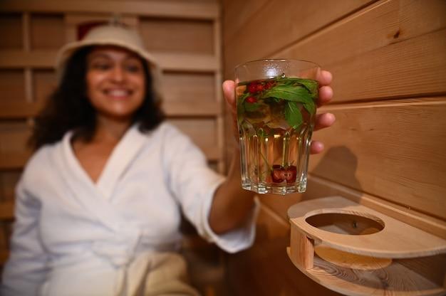 Soft focus su un bicchiere con acqua con menta, bacche e ciliegie nelle mani di una donna sfocata che si rilassa in una sauna in legno