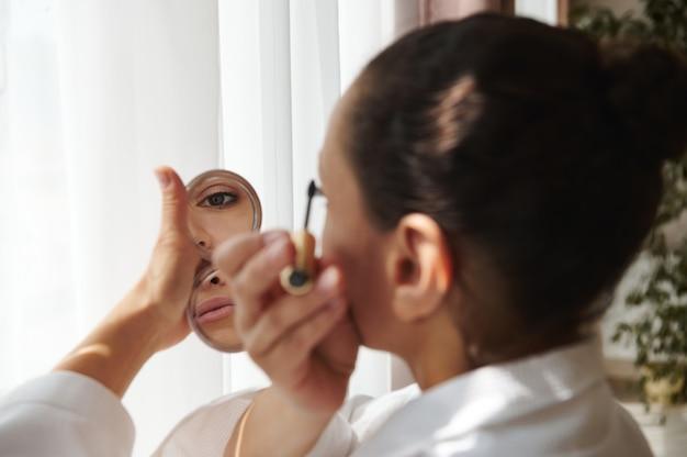Soft focus sul riflesso di occhi e labbra in un piccolo specchio cosmetico nella mano di una bruna che applica il mascara alle ciglia. avvicinamento. concetti di bellezza