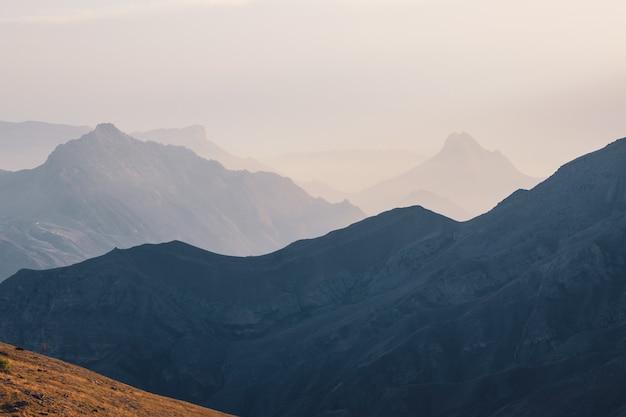 Focalizzazione morbida. paesaggio montano panoramico all'alba con leggera nebbia nella valle tra le sagome delle montagne sotto il cielo nuvoloso. vivido scenario al tramonto o all'alba con nuvole basse nella valle di montagna in colori tenui.
