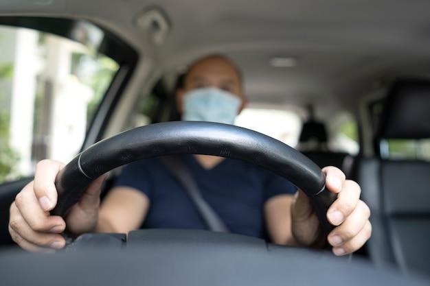Soft focus giovane uomo asiatico con maschera protettiva alla guida di un'auto