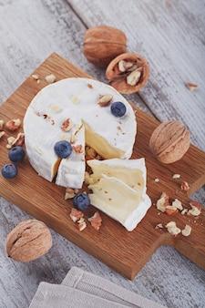 Formaggio francese a pasta molle di camembert servito con noci tritate e mirtilli su piatto di legno.