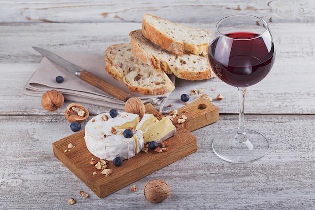 Camembert francese a pasta molle servito con noci tritate bicchiere di vino rosso e mirtilli