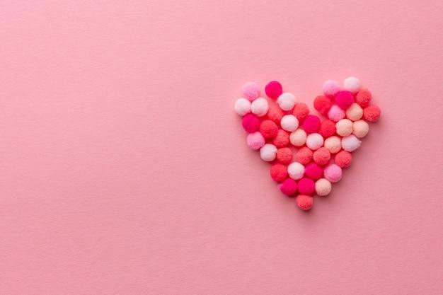 Cuore morbido fatto di soffici pon pon su sfondo rosa per san valentino