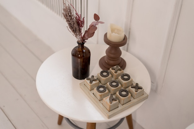 Morbido arredamento per la casa realizzato in vaso di vetro con spighette e giochi di legno sul tavolo bianco. interni.