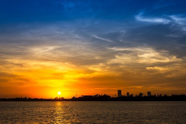 Nuvola morbida e sfocatura di movimento sul cielo blu in riva al fiume al tramonto