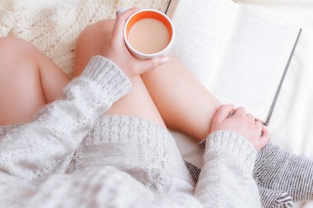 Foto morbida di una donna in un maglione accogliente sul letto con il vecchio libro e una tazza di tè con il latte nelle loro mani
