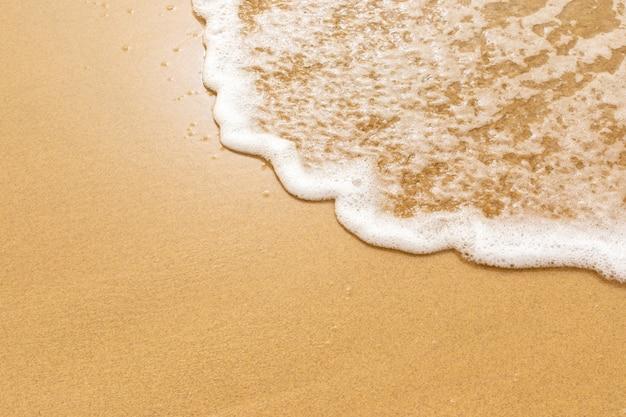 Morbida onda del mare sulla sabbia dorata.