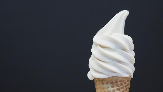 Cono gelato soft servire su sfondo nero. (avvicinamento )