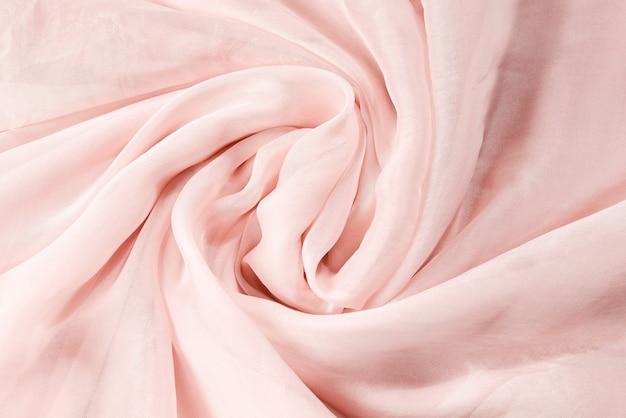 Sfondo morbido tessuto di seta rosa liscia.