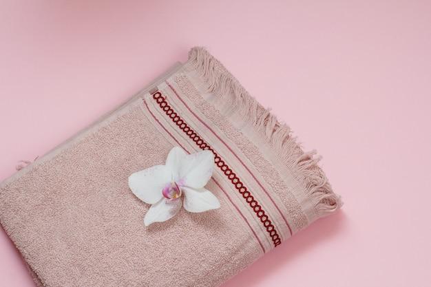 Asciugamano in morbida spugna con gemma di orchidea bianca su sfondo rosa. vista dall'alto.