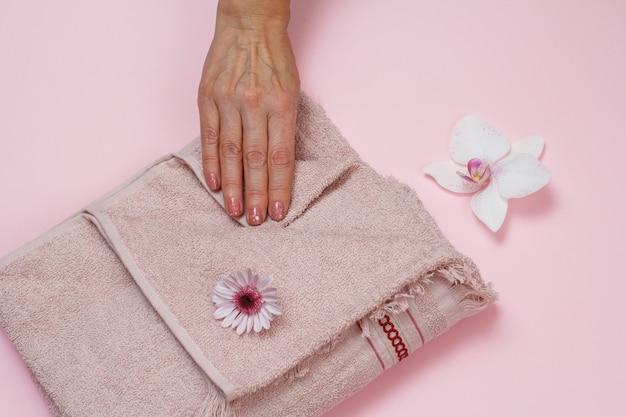 Asciugamano in morbida spugna e mano di donna con fiori su sfondo rosa. vista dall'alto.