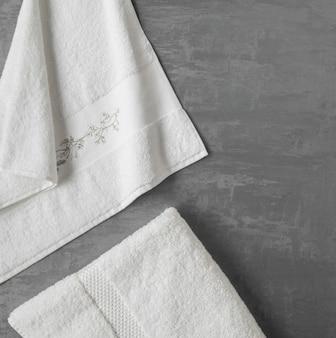 Asciugamano morbido in uno sfondo di stucco decorativo grigio. vista dall'alto, isolata