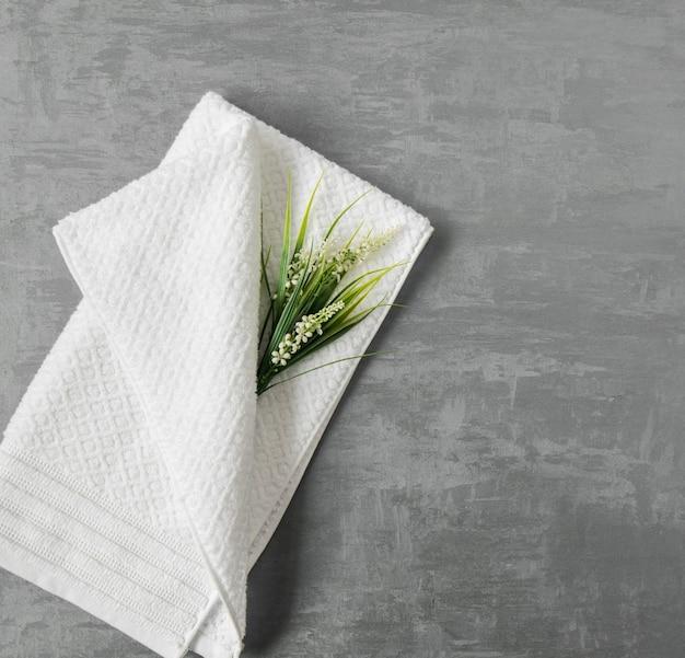 Asciugamano morbido con un fiore su uno sfondo di stucco decorativo grigio. vista dall'alto, isolata