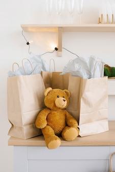 Orso di peluche vicino a sacchetti di carta artigianale