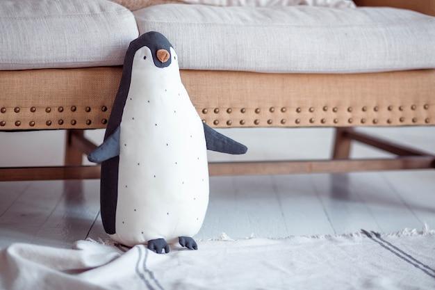 Pinguino di peluche si trova vicino al divano sul pavimento