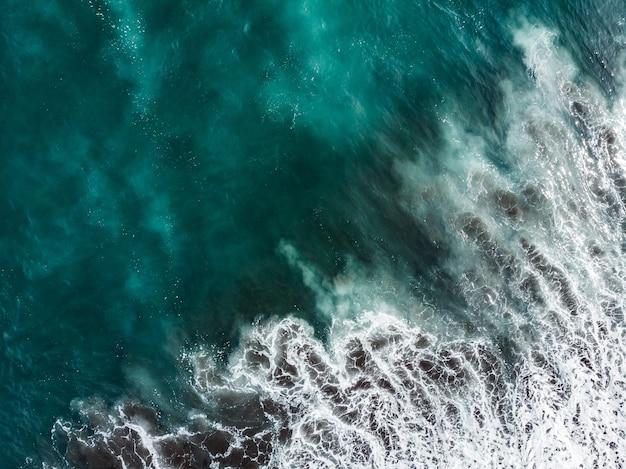 Morbida onda di oceano blu sulla spiaggia sabbiosa. sfondo.