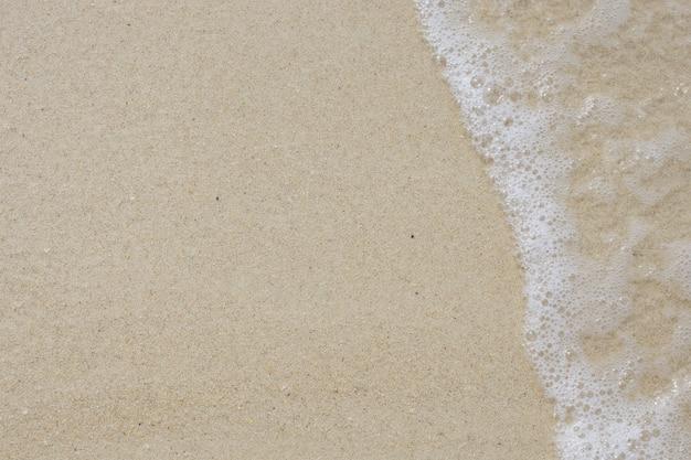 Morbida onda del mare sulla spiaggia sabbiosa