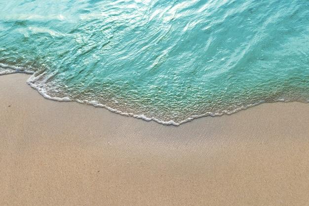 Onde morbide con schiuma di oceano blu sulla spiaggia sabbiosa.