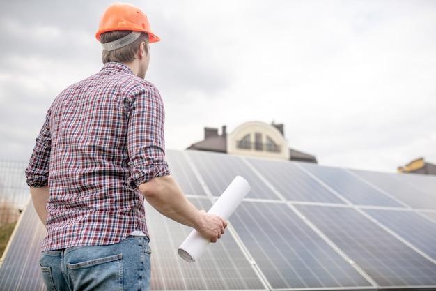 Batteria solare. uomo con casco di sicurezza arancione con disegno con le spalle alla telecamera guardando il pannello solare vicino alla casa di campagna