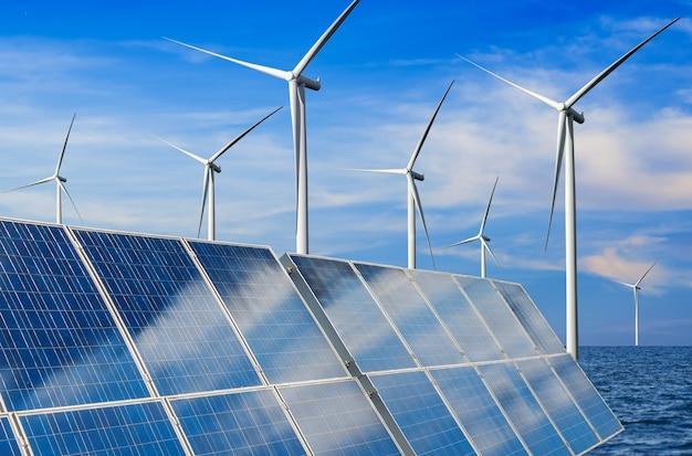 Cella fotovoltaica del pannello di energia solare e generatore di potenza dell'azienda agricola della turbina di vento nel paesaggio della natura.