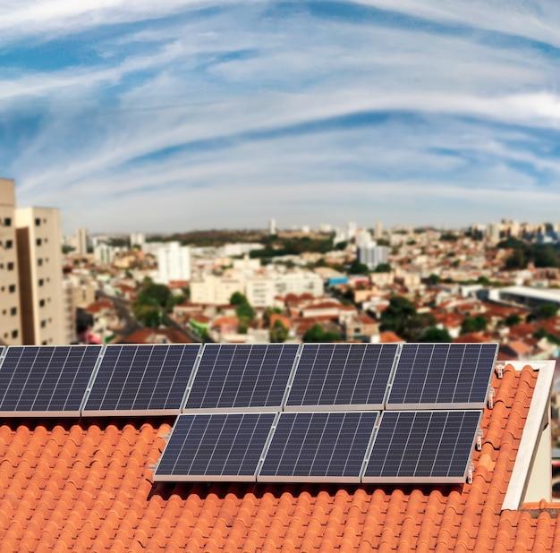 Pannelli a energia solare su un bellissimo sfondo della città del cielo al tramonto. spazio per il testo. Foto Premium