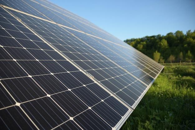 Pannello solare su sfondo azzurro del cielo. fotovoltaico, fonte di energia elettrica alternativa. idea per le risorse sostenibili.concetto di energia di potenza alternativa.azienda solare sull'erba verde