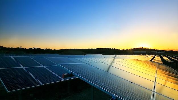 La cella del pannello solare sul drammatico sfondo del cielo al tramonto pulisce il concetto di energia alternativa