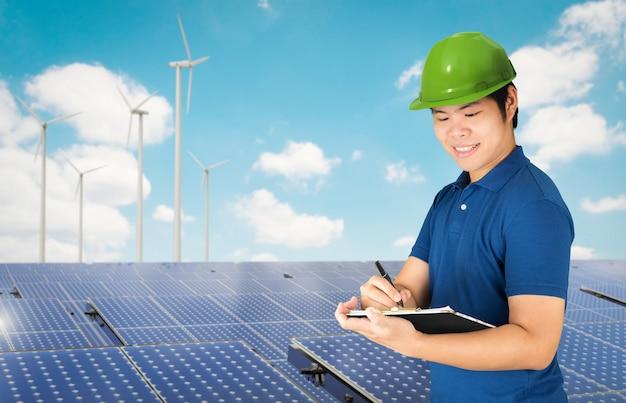 Tecnico pannelli solari con pannello solare e turbine eoliche