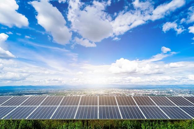 Pannello solare con la costruzione moderna della città della città di campagna e il fondo dei grattacieli, concetto di energia alternativa pulita.