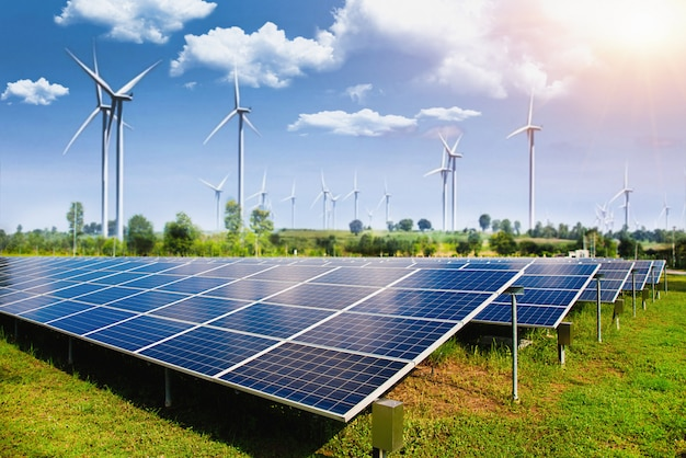 Pannello solare con turbine eoliche contro montagne e cielo