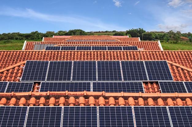 Installazione di pannelli solari sul tetto di molte case in una giornata soleggiata e nuvolosa. immagine del concetto di energia solare fotovoltaica.