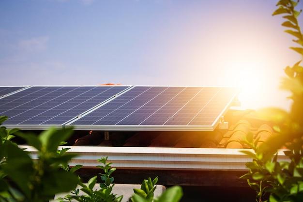 Pannelli solari sul tetto rosso in una giornata soleggiata e nuvolosa. immagine dell'impianto fotovoltaico.