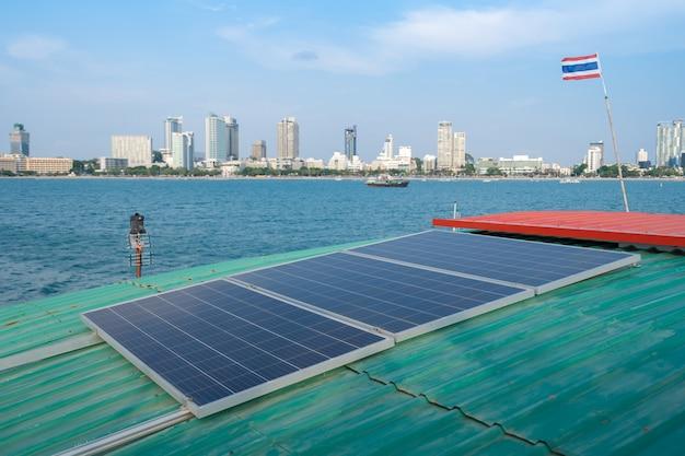 Pannelli solari sul tetto di una zattera galleggiante o di una nave in mare vicino alla costa della città con una piccola bandiera tailandese. produrre elettricità in un concetto di tecnologia pulita.