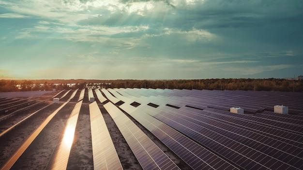 Pannelli solari con pannelli solari a cielo drammatico con sfondo riflesso del sole di moduli fotovoltaici