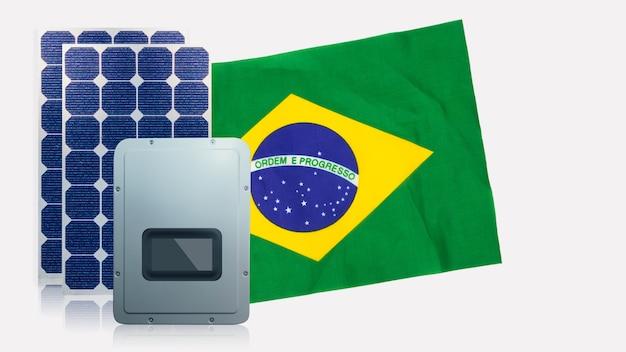 Pannelli solari fotovoltaici, invertitore e bandiera del brasile isolati su sfondo bianco. spazio per il testo