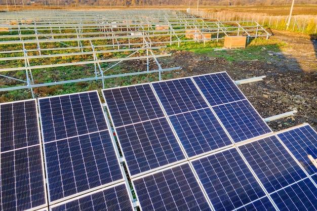 Centrale solare in costruzione sul campo verde. assemblaggio di quadri elettrici per la produzione di energia pulita ed ecologica.